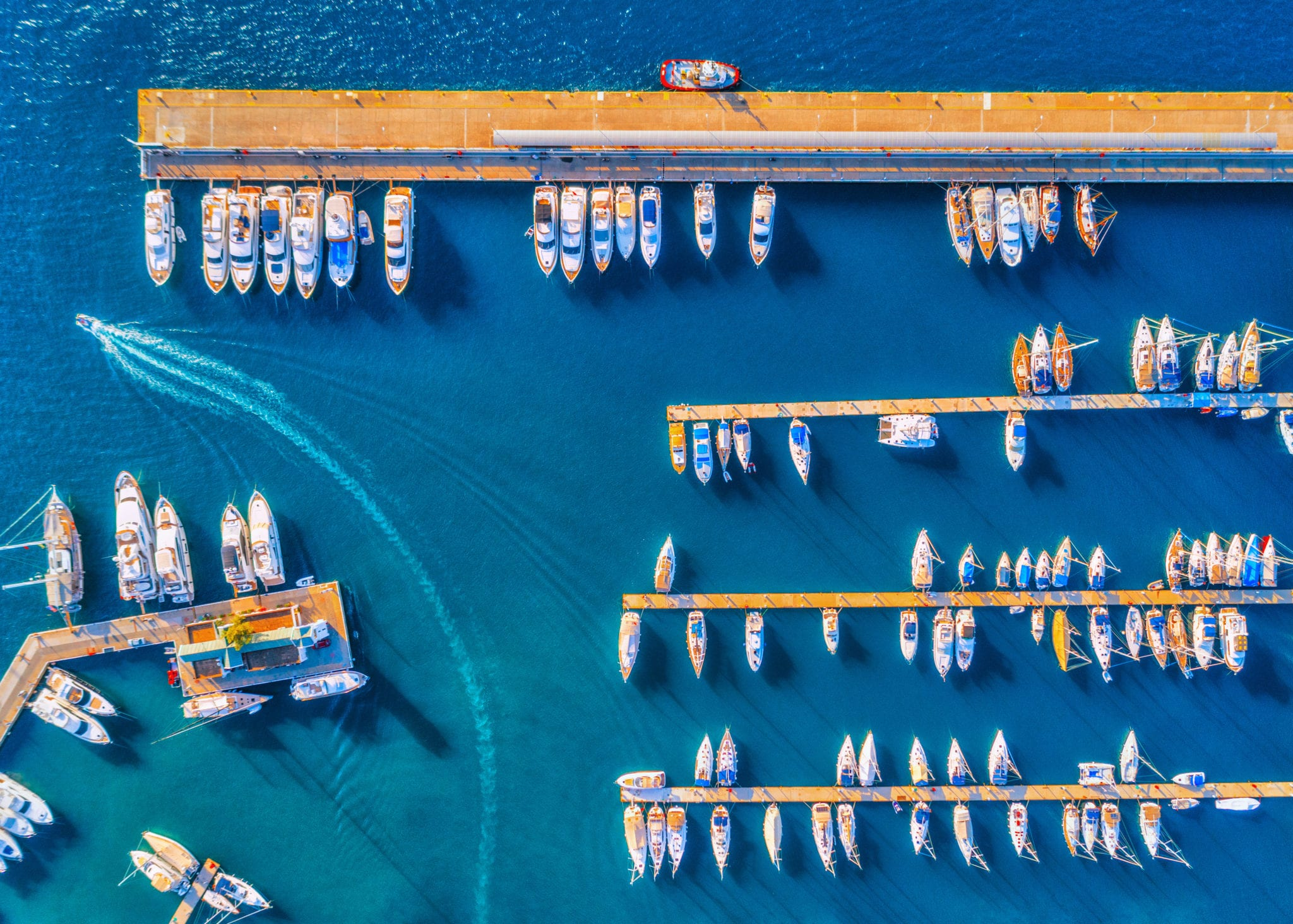 Aerial view of beautiful boats at sunset in summer. Minimalistic landscape with boats and sea in marina bay. Top view from drone of harbor with yacht, motorboat and sailboat. Beautiful port. Travel